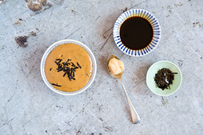 A bowl of lght brown Japanese Tahini dressing on a distressed metal background. Next to the bowl is a dipping bowl of tamari, a reaspoon of white miso paste and a small green bowl if finely chopped nori