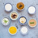 8 small bowls of tahini dressing on a discressed metal background viewed from above.
