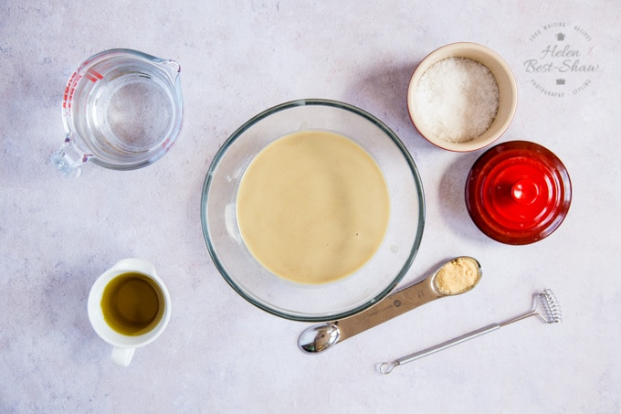 Overhead show of a bowl of tahini, red por containind sea salt, small white jug of olive oil, spoon of garlic powder, glass jug of water and a whisk