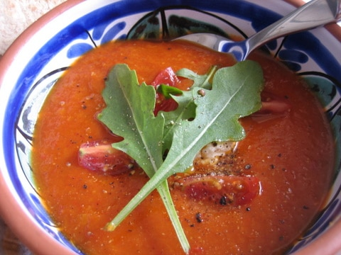A bowl of vibrant red roasted pepper, tomato and red lentil soup.