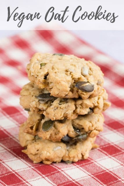 """A stack of 4 seeded oat cookies on a red check table cloth. Text overlay reading """"Vegan Oat Cookies"""""""
