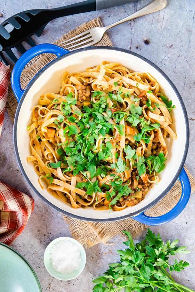 A casserole dish of lentil ragu stirred through cooked tagliatelle