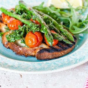 A green plate with asparagus topped bruschetta and roasted tomatoes