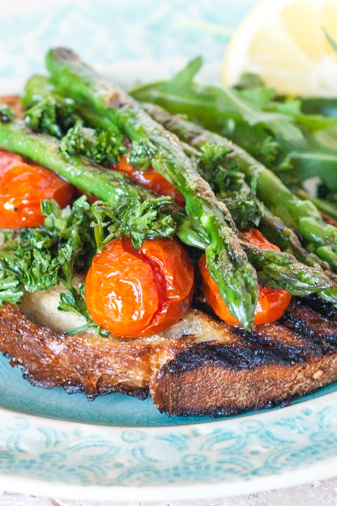 A plate of bruschetta toped with griddled asparagus, garnished with chopped herbs and cherry tomatoes