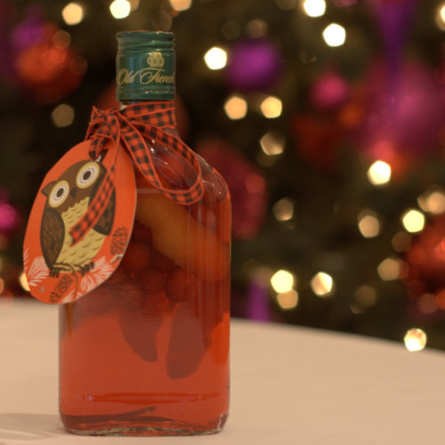 A bottle of deep red coloured Christmas spiced vodka. The bottle contains orange peel and spices. There is a Christmas tree in the background and a gift label tied to the bottle with a tartan ribbon
