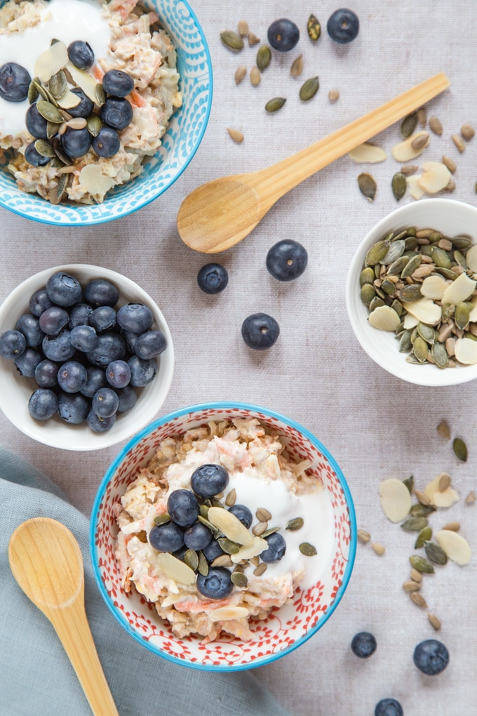 A top down view of a table set with two bowls of bircher muesli, seeds and blueberries
