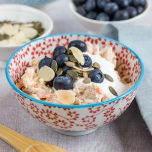 A table set with a bowl of bircher muesli served with blueberries and seeds