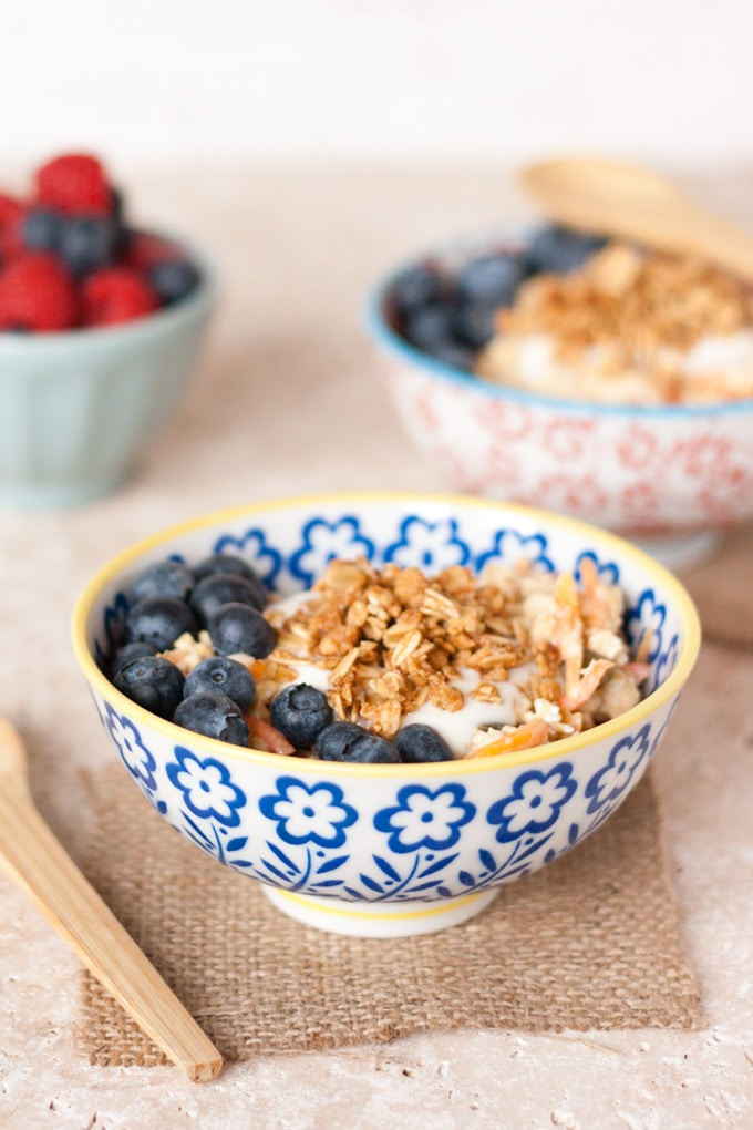 A blue and white floral bowl of bircher muesli topped with granola