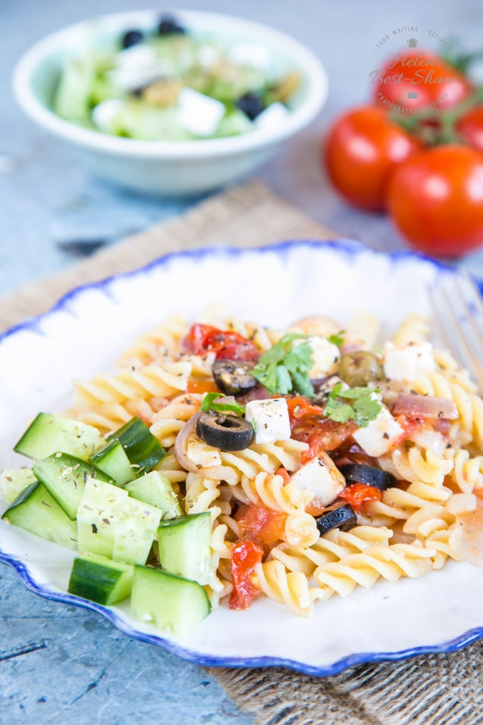 A plate of Greek salad pasta and cucumber. Pasta sauce made with olives, tomato, feta and onion