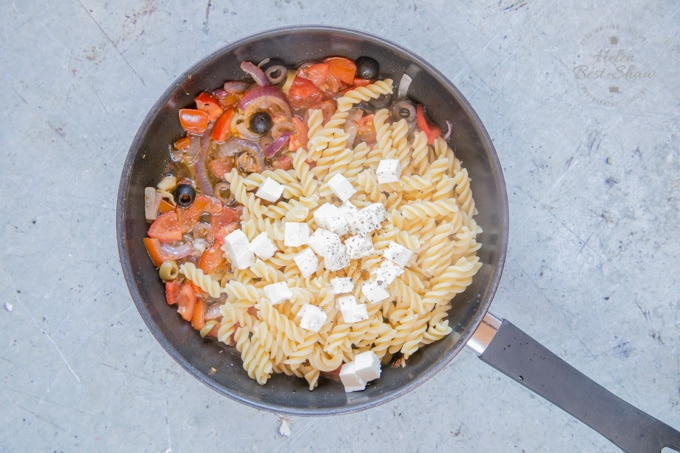 Greek salad pasta – step three – a pan of red onions and garlic fried until they are soft. Tomatoes and olives have also been added to the pan along with pasta and diced feta