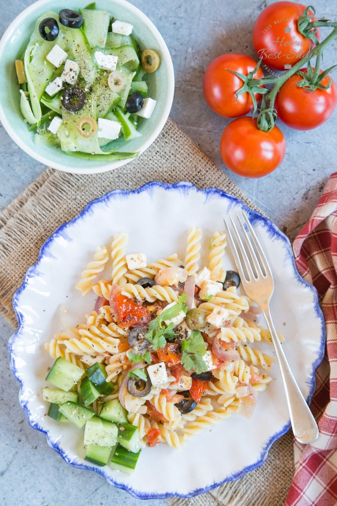 Top down view of a plate of Greek Salad Pasta – served with a tomato, feta, red onion and garlic sauce