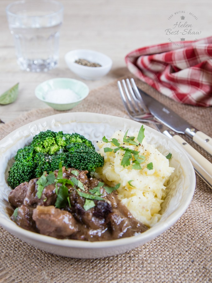 A bowl of beef stew in a rich dark sauce. Served with mashed potato and brocolli