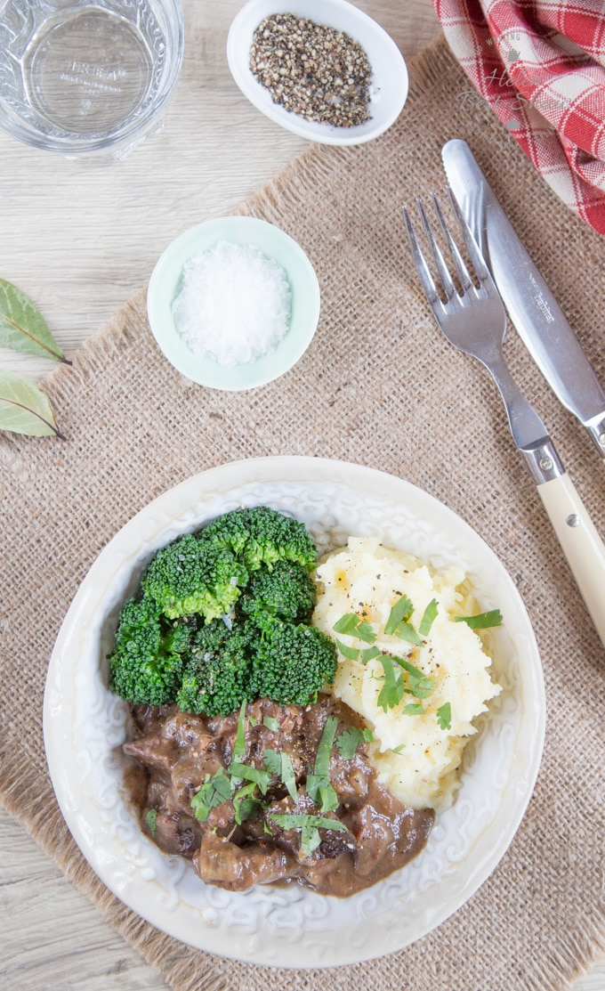 A bowl of beef stew in a rich dark sauce. Served with mashed potato and broccoli- viewed from above