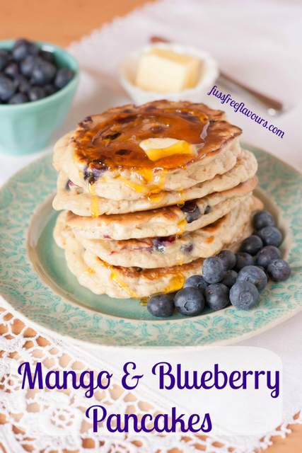 Mango blueberry pancakes with syrup captioned