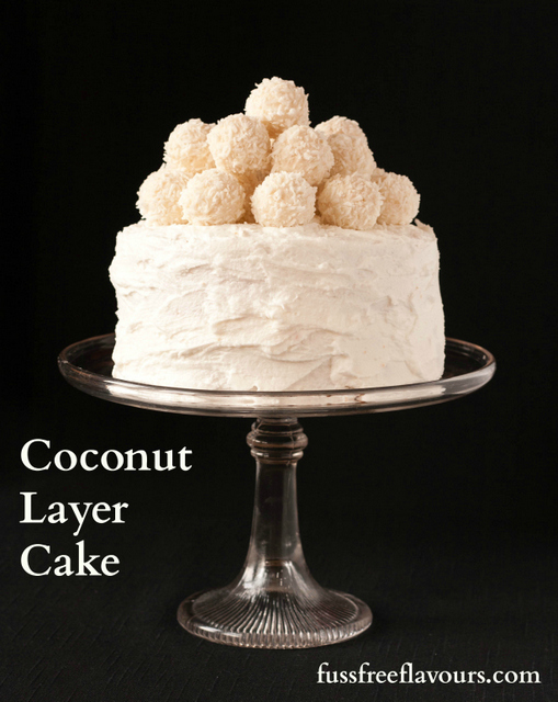 An indulgent coconut cake, made with coconut sponge, covered with coconut frosting and topped with Ferrero Raffaello coconut truffles