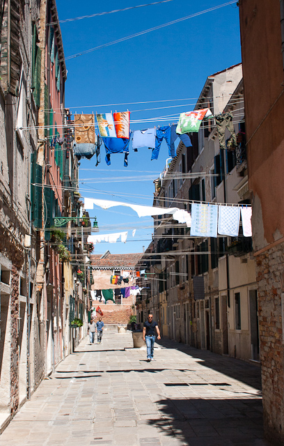 Washing drying flapping in the streets above pedestrians' heads.  Castello Quarter, Venice