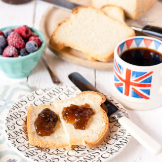 A plate with a slice of white yogurt bread spread with butter and jam. so shown is a loaf of bread, dish of berries and cup of coffee