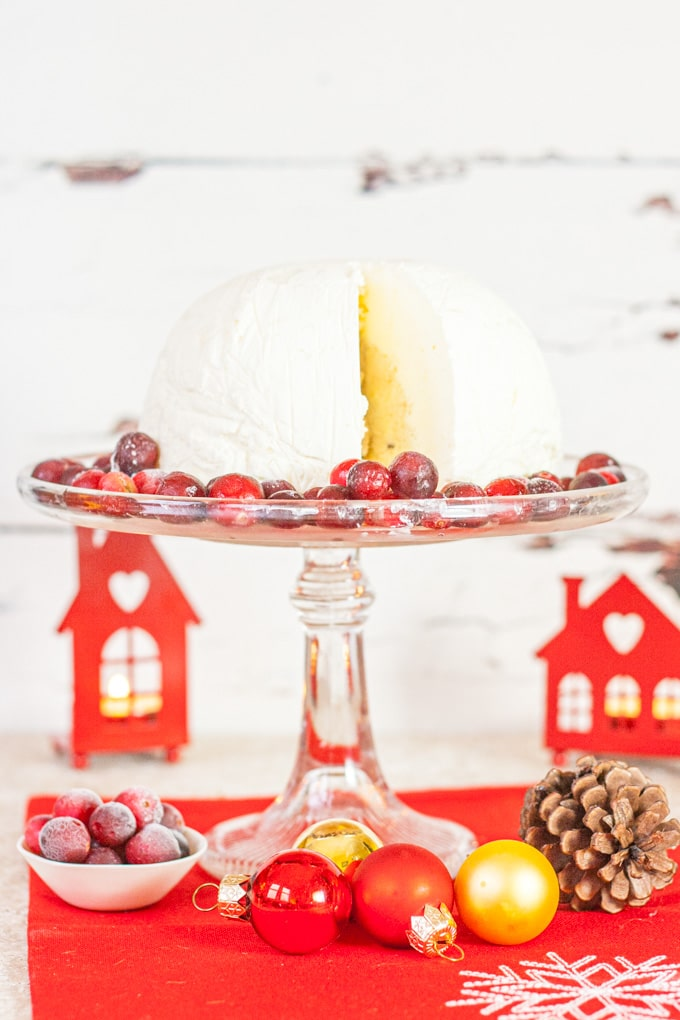 A Christmas pudding ice cream bombe on a glas cake stand with a slice cut out