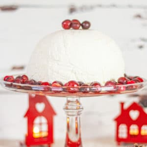 A glass cake stand with a domed white ice cream bombe on it, garnished with cranberries