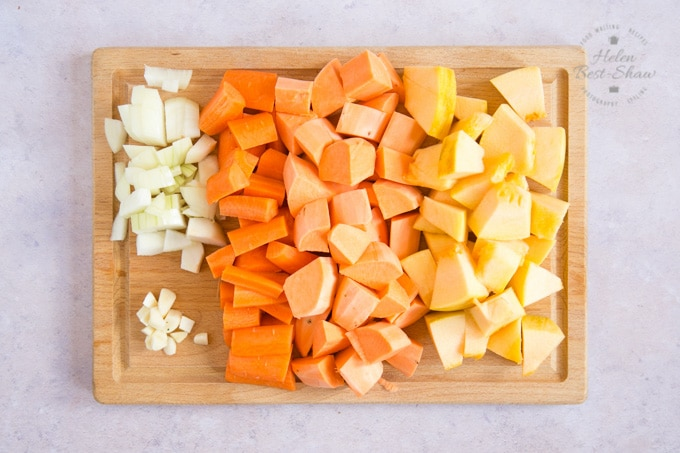 A wooden chopping board with chopped carrot, pumpin, sweet potato, onion and garlic.