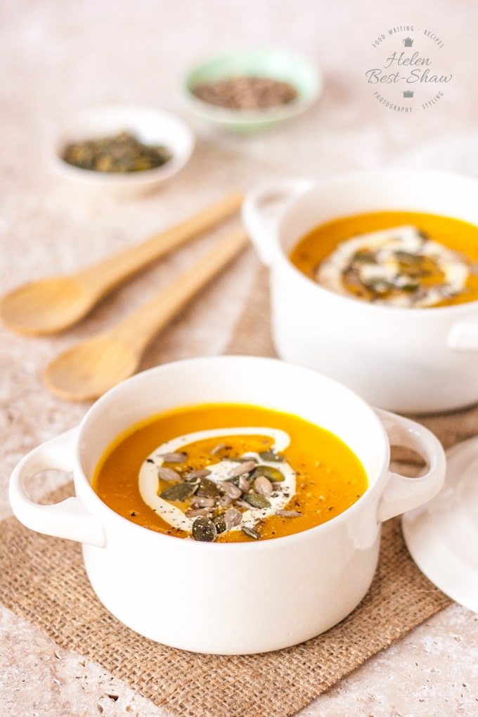Two white bowls of golden orange pumpkin, carrot and sweet potato soup, drizzled with cream and toasted seeds