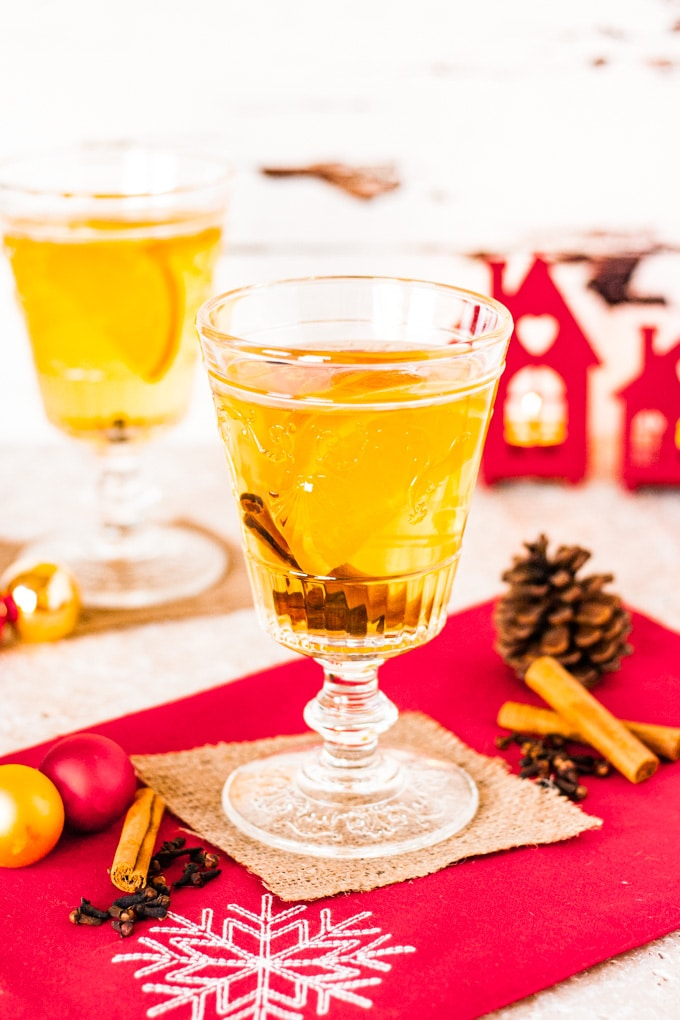 A glass of mulled cider garnished with a slice of orange and a cinnamon stick