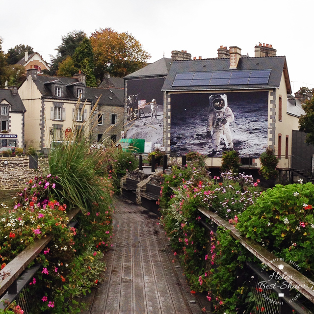 Images of the moon landings covering the side of a house at Festival Photo at La Gacilly