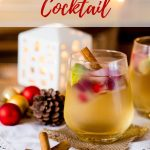 A gin and apple christmas cocktail in a clear glass with a cinnamon stick decorated with christmas decorations
