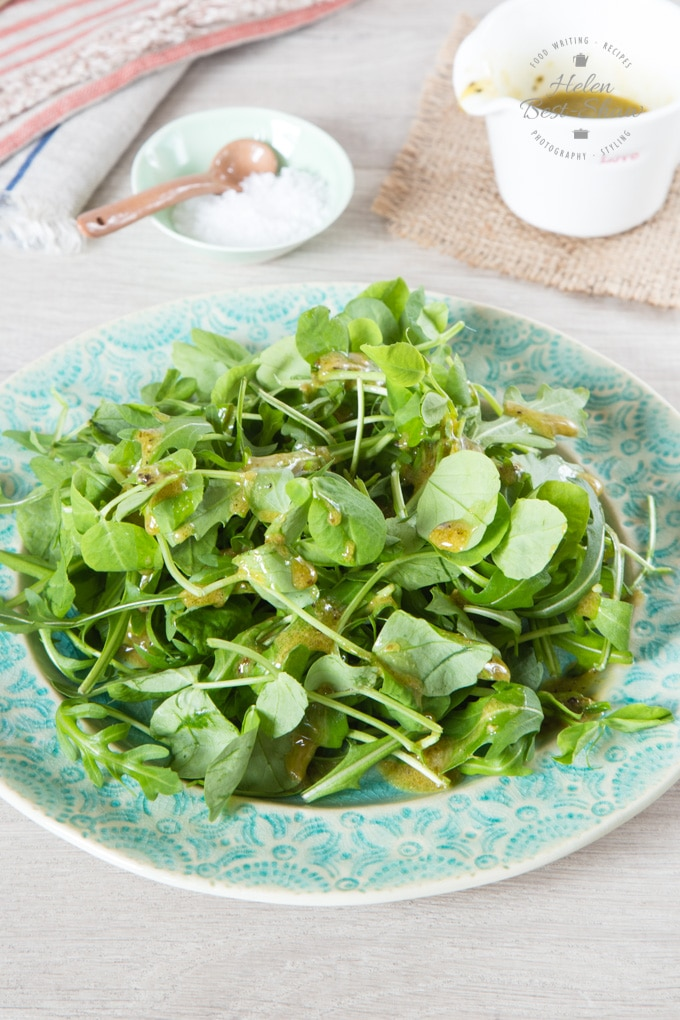 A plae of green salad with pesto salad dressing