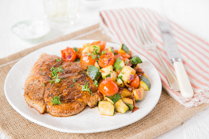A plate with a Southern spiced pork steak on with a side serving of ratatouille