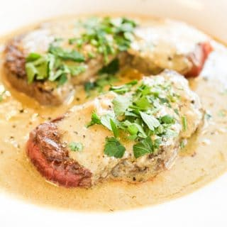 Two steaks on a plate surrounded by a Stilton sauce and garnished with chopped parsley