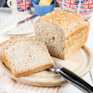 Two slices and a loaf of bread made with leftover oatmeal on a bread board on a table set for breakfast with a Union Jack teapot and mug