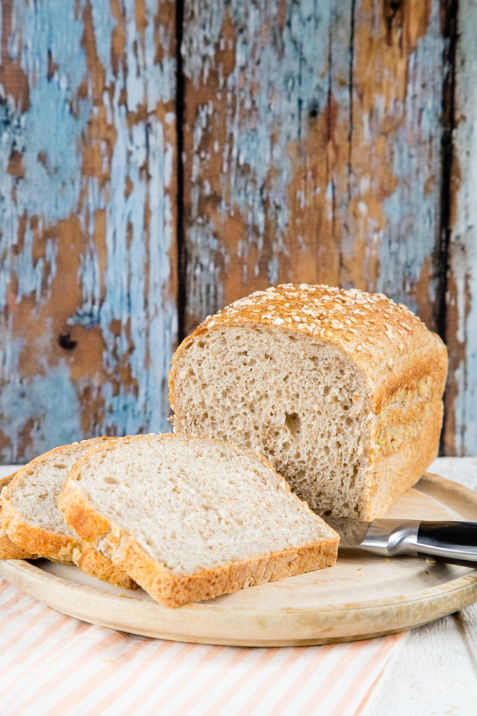 Two slices and a loaf of bread made with leftover oatmeal on a bread board on a table with a blue wood background behind