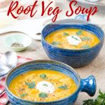 Two blue ceramic bowls containing golden yelllow fat free root veggie soup. the soup is garnished with sour cream and chopped herbs. Text overlay reads slow cooker root vegetable soup & fat free & vegan,