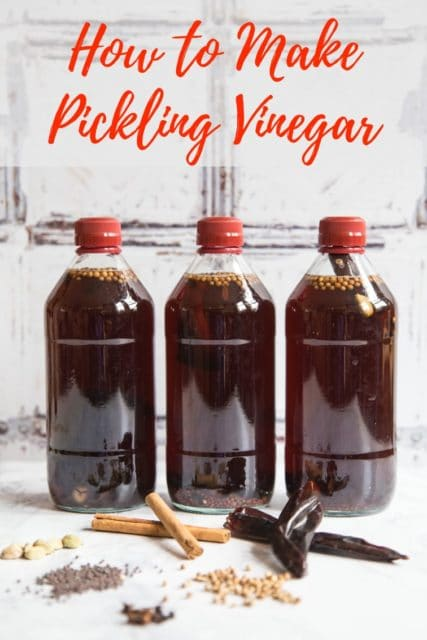 3 bottles of spiced vinegat for pickling standing on a marble background. A selection of spices including chillies, cinnamon sticks, cloves and cardamon pods are arranged in front. Text overlay readinf How to make pickling vinegar
