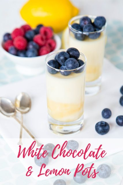 Two shot glasses containing a layered lemon curd and white chocolate pudding. The scene also shows two silver spoons, a bowl of berries and a lemon. Text overlay reads White chocolate & Lemon Pots.