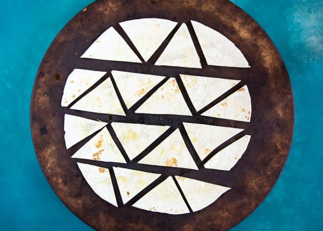 To make our baked crispy homemade tortillas, cut the strips of wrap into triangles