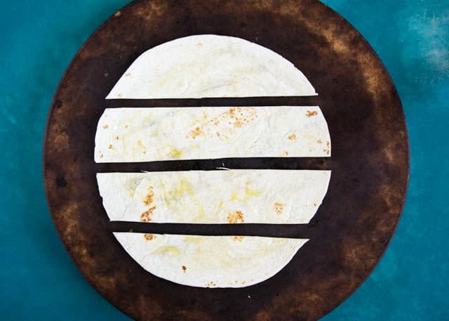 To make our baked crispy homemade tortillas, first cut a wrap into strips