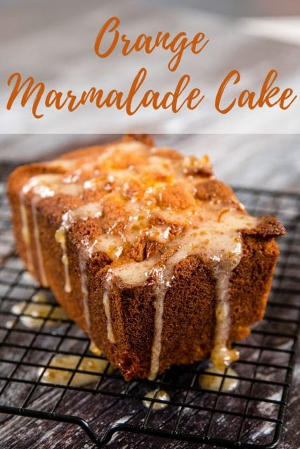 A delicious, sticky orange marmalade loaf cake dripping with marmalade drizzle sitting on a wire cooling rack. Text overlay reads Orange Marmalade Cake