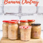 7 jars of freshly homemade banana chutney standing on a wooden board. Text overlay reading Homemade Banana Chutney
