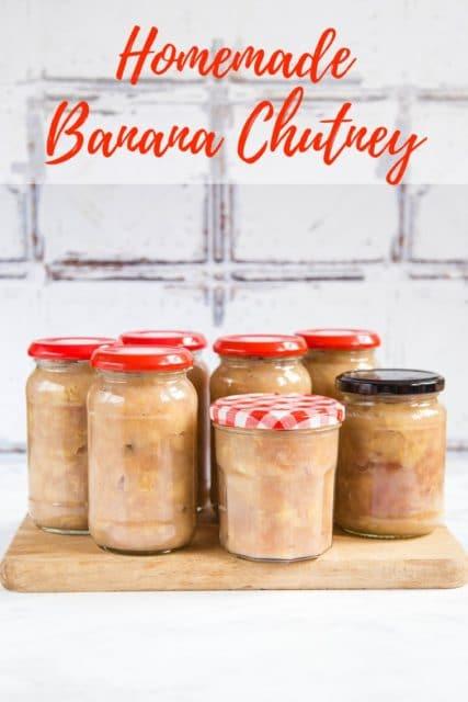 7 jars of freshly homemade banana chutney standing on a wooden board. Text overlay reading Homemade Banana Chutney