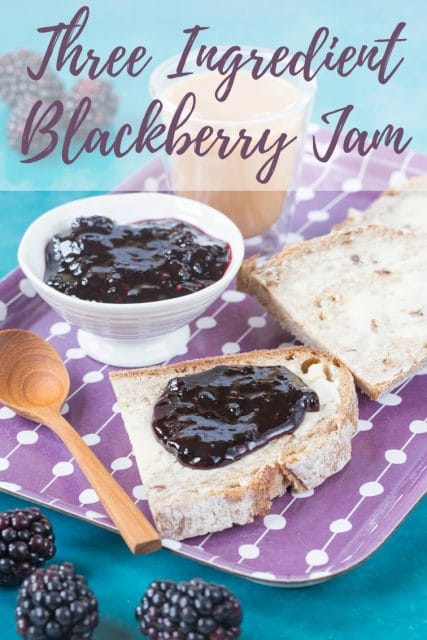 "A slice of bread spread with butter and backberry jam on a purple patterned tray. in the backgorund there is a pot of jam and some more slices of bread. Text overlay reads ""Trhee ingredient blackberry jam"""