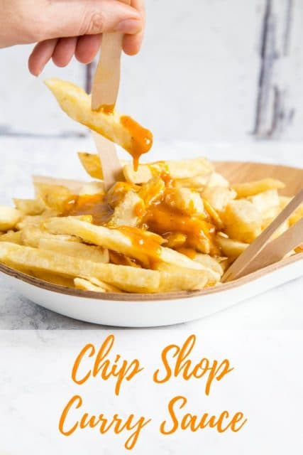 A plate of chip shop fat chips covered with golden brown Chinese curry sauce. A hand holds a chip fork with a single chip on it with the sauce dripping off. Text overlay reads Chip Shop Curry Sauce.
