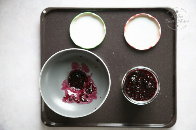 Two freshly filled jars of blackberry jam viewed from above. Once