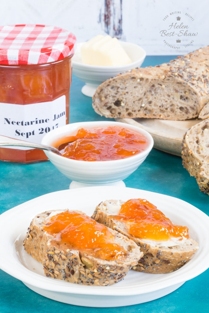 A blue table top is set with a white plate with two slices of brown seeded bagette topped with butter and golden orange small batch nectarine jam. Behind the plate there is a small white bowl and a jar of of nectarine jam. Also in the background there is a breadboard with a cut brown baguette on it.
