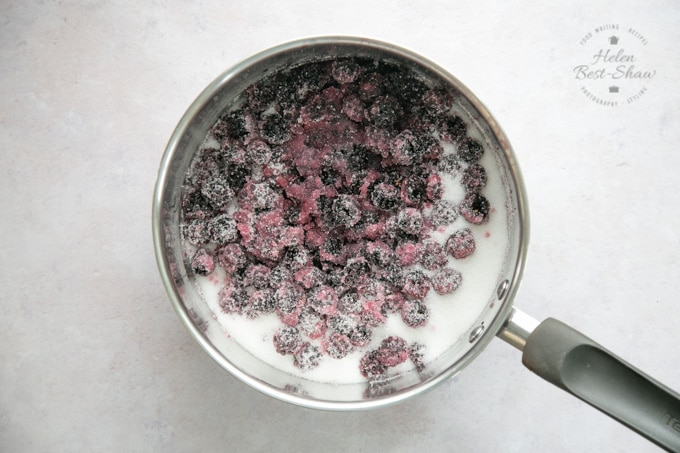 A saucepan viewed from above filled with blackberries and sugar