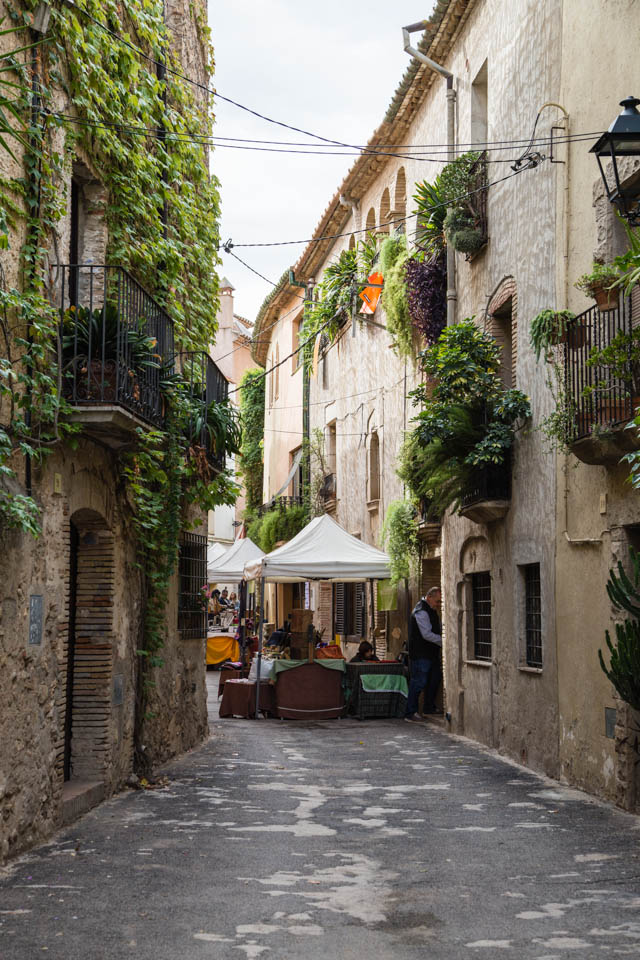 Shaded street in Ventalló, Catalonia with market stalls
