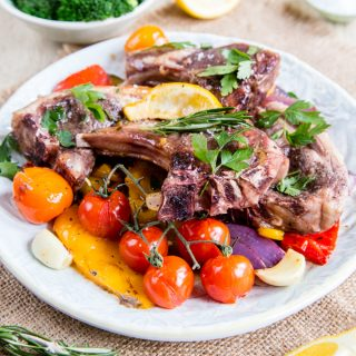 A plate of colourful roast Mediterranean vegetables, topped with roast lamb chops and garnished with parsley.