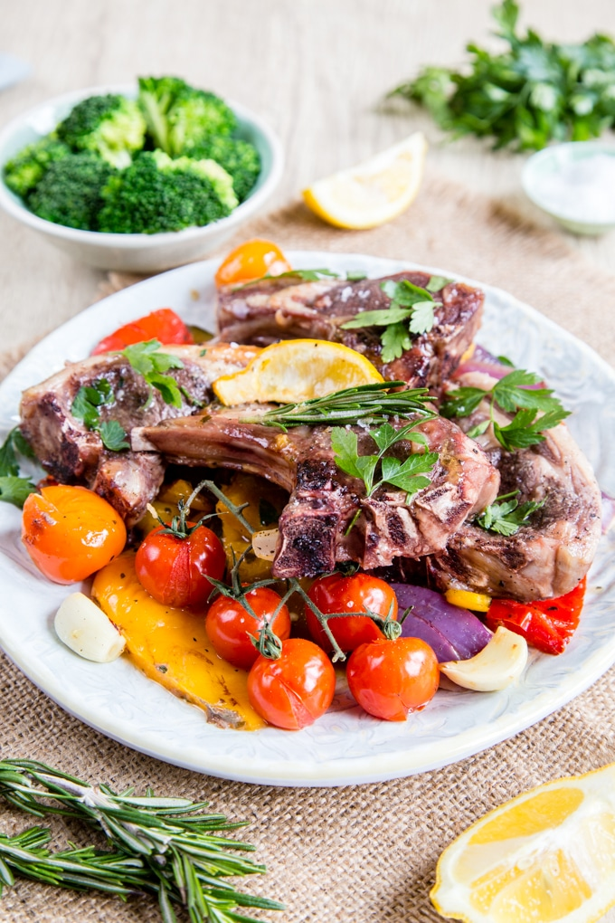 A plate of roast red and yellow Mediterranean vegetables topped with glazed lamb chops, garnished with parsley. Served with a dish of broccoli.