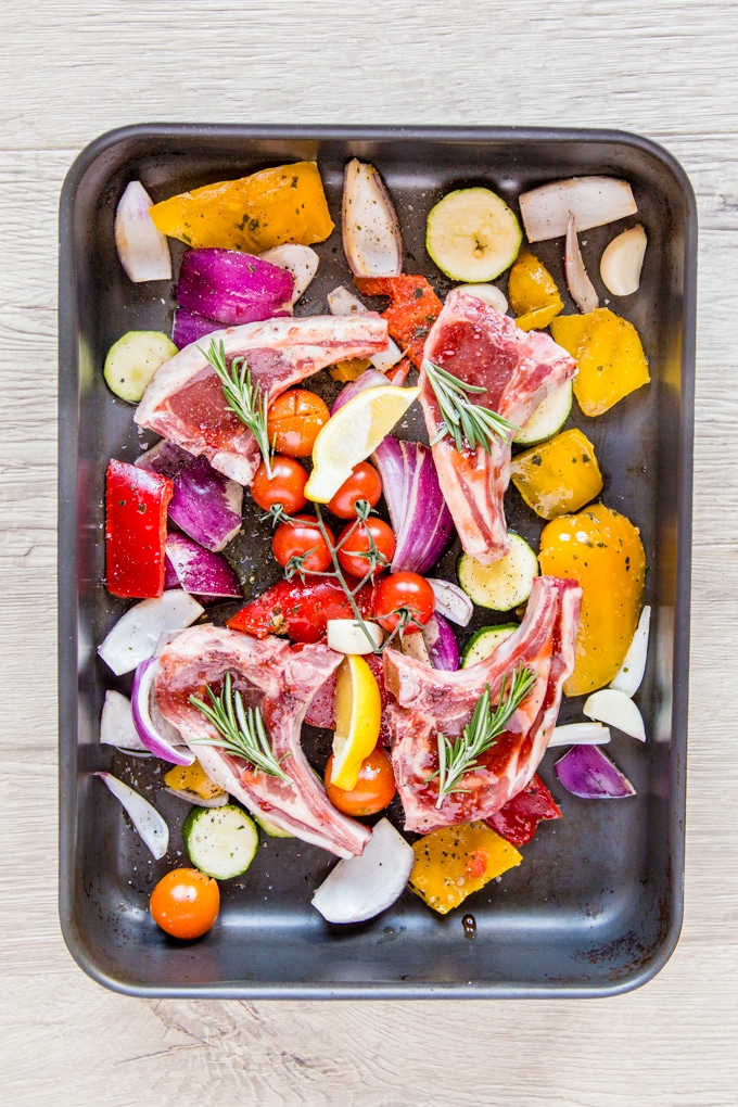 A roasting dish full of Mediterranean vegetables and glazed lamb chops